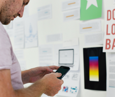 Foreground: Man in white shirt looking at his phone. Background: Marketing material hangs on a white board.