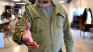 A man holds out his hand in preparation for a handshake.
